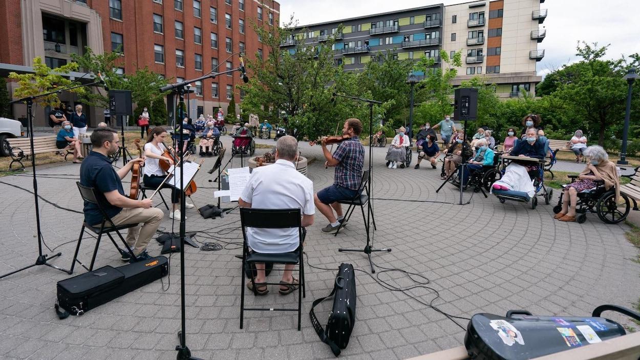Des musiciens et musiciennes jouent à l'extérieur.