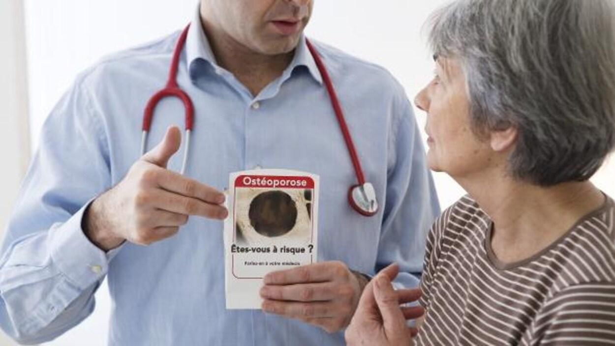 Un médecin parle à une patiente. Il tient une brochure qui dit : Ostéoporose, êtes-vous à risque?