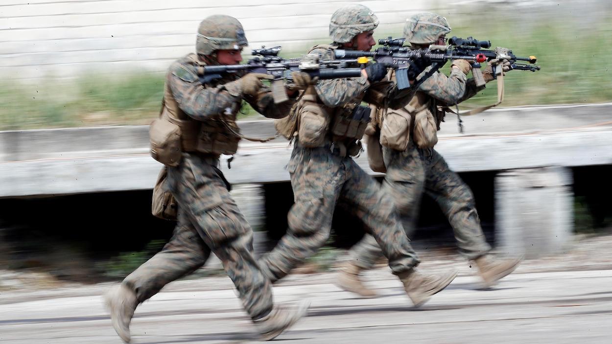 Trois soldats courent en pointant leur fusil d'assaut dans les rues d'un village en Lituanie.