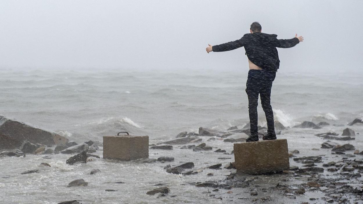 Un homme debout sur un bloc de béton fait face à l'océan et aux vents violents.
