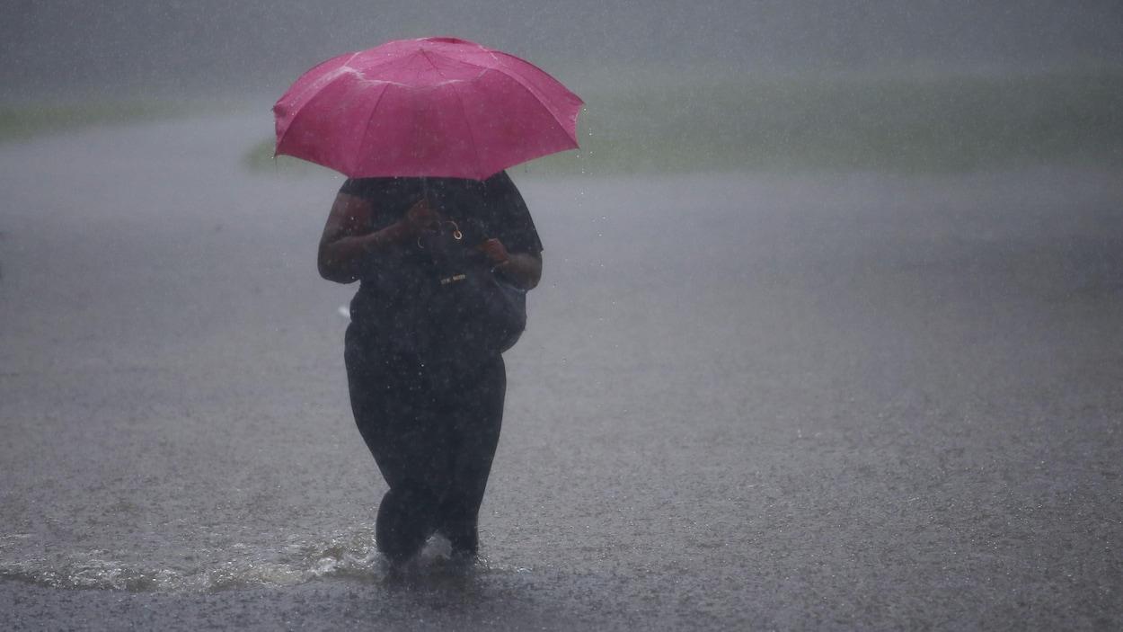 Une femme marche dans une rue inondée, avec de l'eau jusqu'aux genoux, alors que la pluie s'abat sur elle et son parapluie rose.