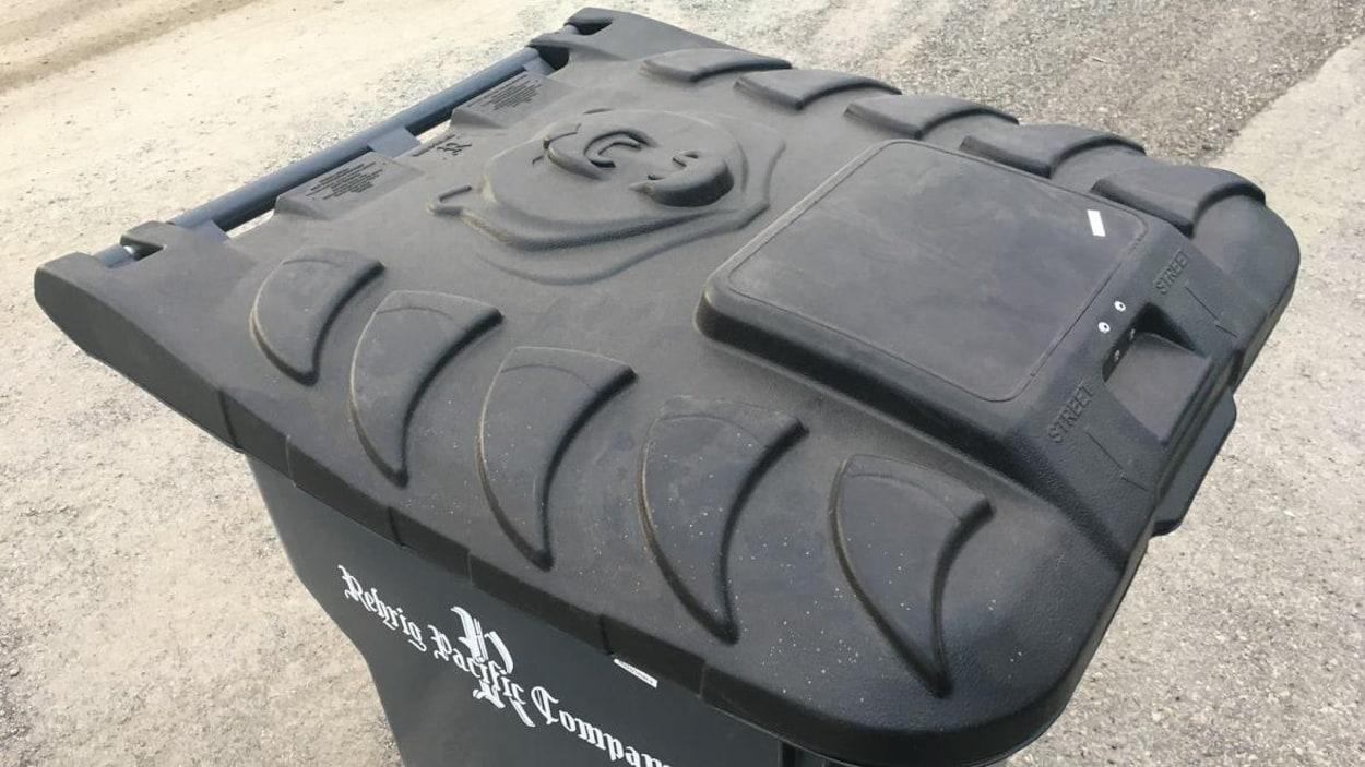 Une poubelle noire avec un dessin d'ours sur le couvercle.