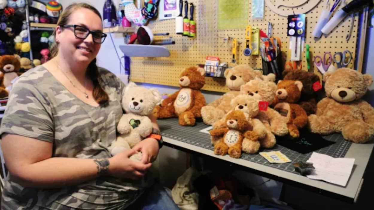 Une femme tient un ourson en peluche dans ses mains.