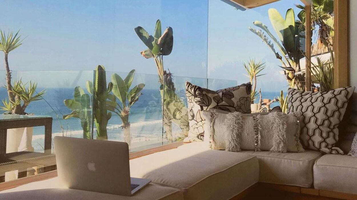 Un ordinateur portable posé sur un sofa près d'une fenêtre avec vue sur la mer.