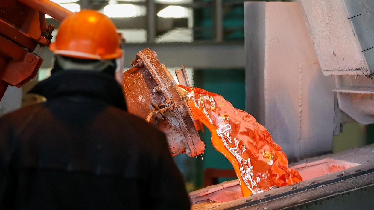 Un ouvrier observe une coulée d'aluminium dans un moule.