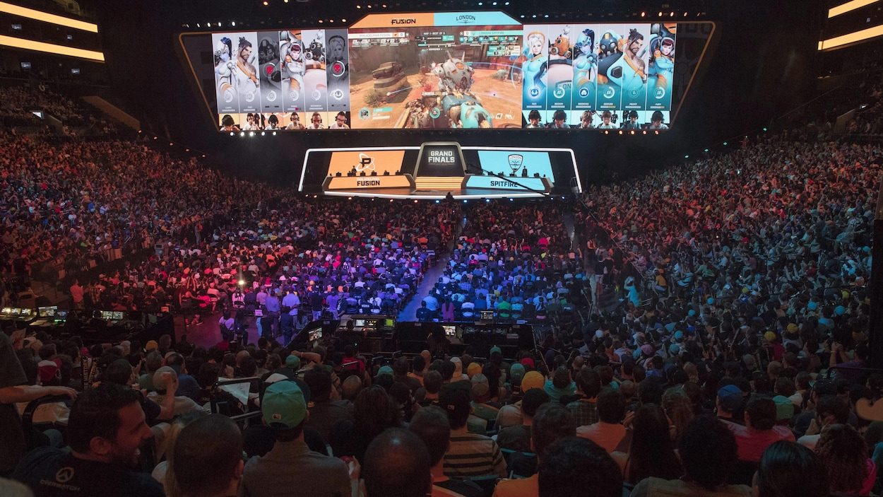 Une foule de plusieurs milliers de personnes massés dans les gradins d'un aréna regardent une scène et des écrans géants affichant une partie du jeu vidéo Overwatch.