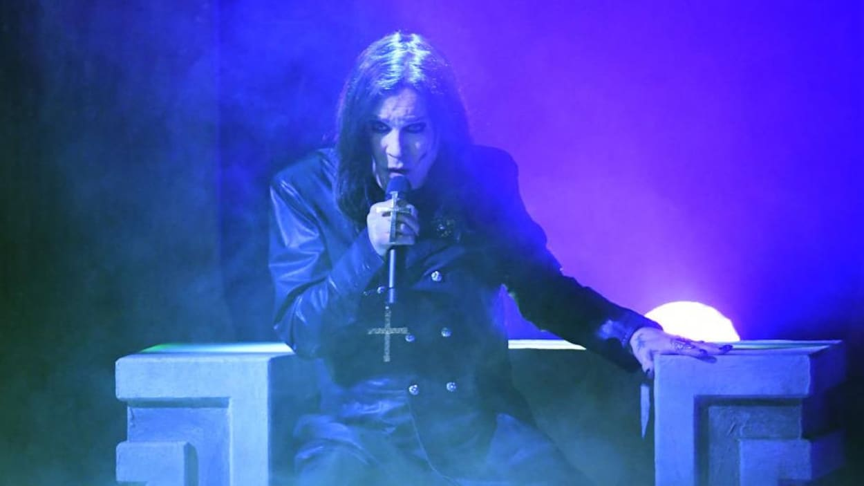 Ozzy Osbourne, sur scène, tient un micro et porte une croix.