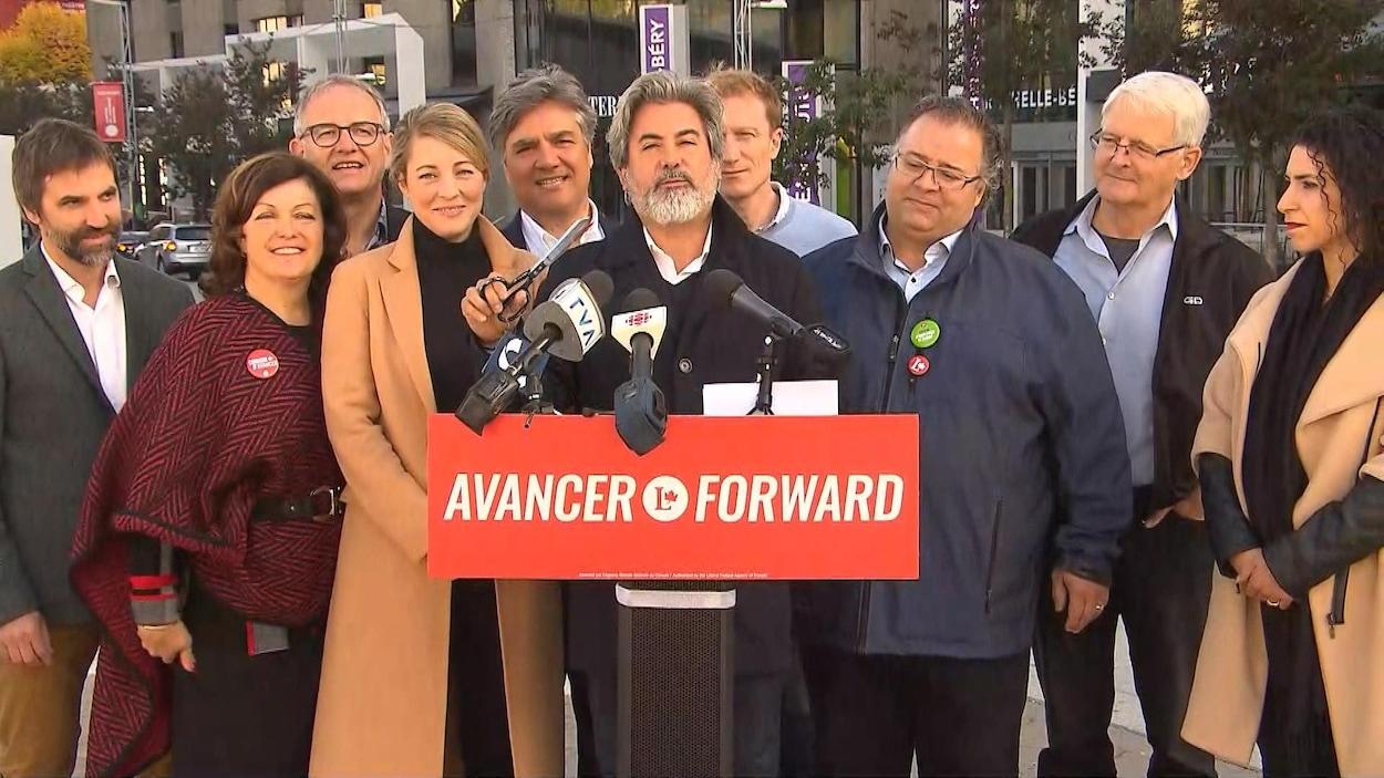 Entouré d'autres candidats libéraux, Pablo Rodriguez tient une paire de ciseaux.