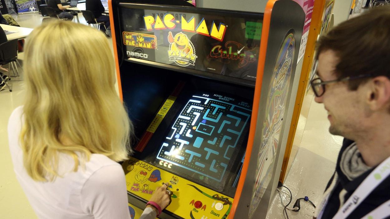 Une femme joue à une version arcade du jeu Pac-Man.