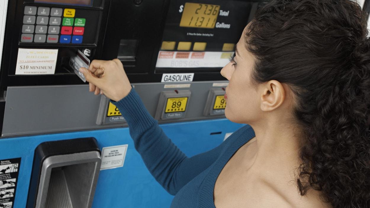 Une femme paie par carte à la pompe d'une station-service.
