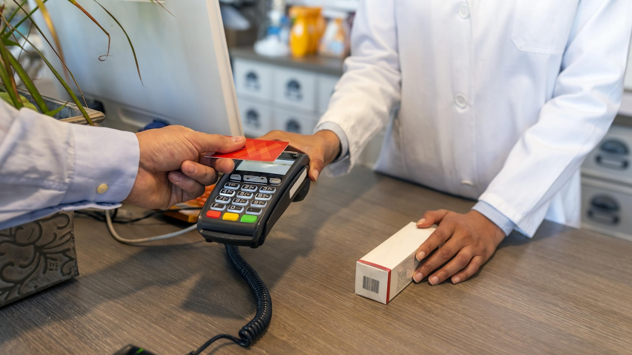 Un homme procède à un achat avec une carte de crédit.