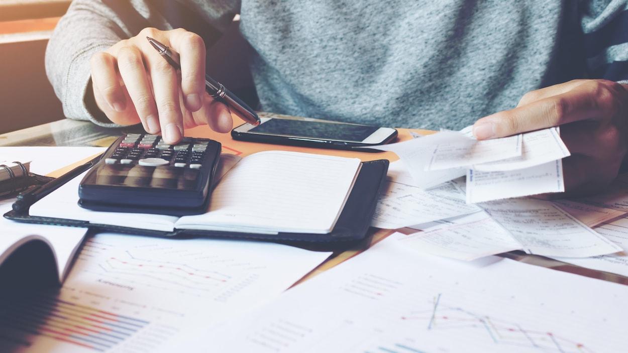 Ue personne utilisant une calculatrice et consultant ses factures.