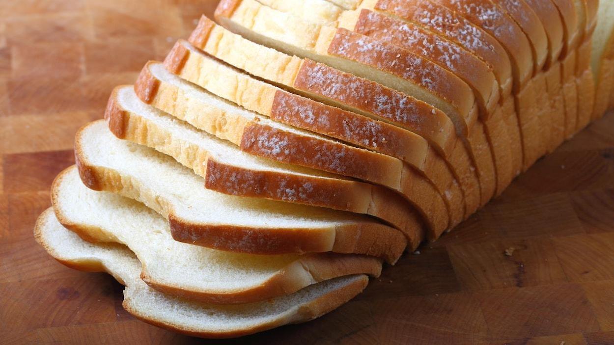 Du pain italien tranché est disposé sur une planche de bois.