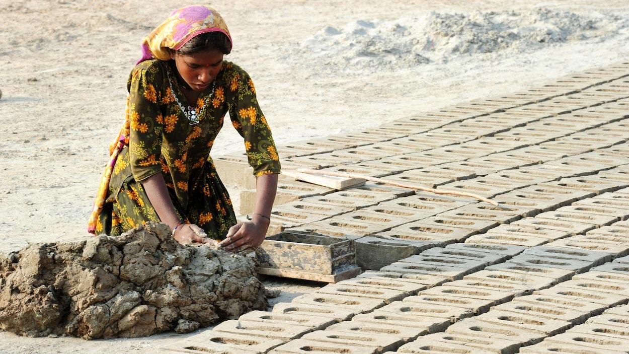 Une femme agenouillée aligne des briques sur le sol.