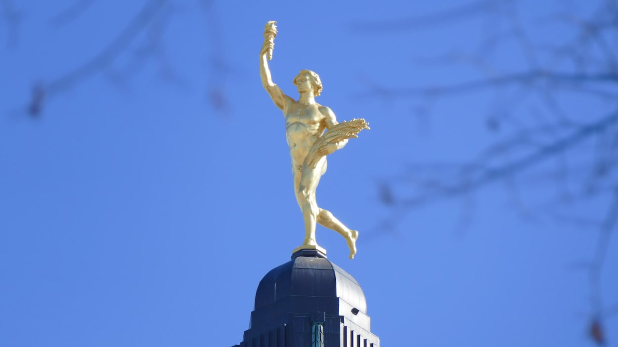 La statue Golden Boy surplombe le palais législatif du Manitoba sous un ciel dégagé.