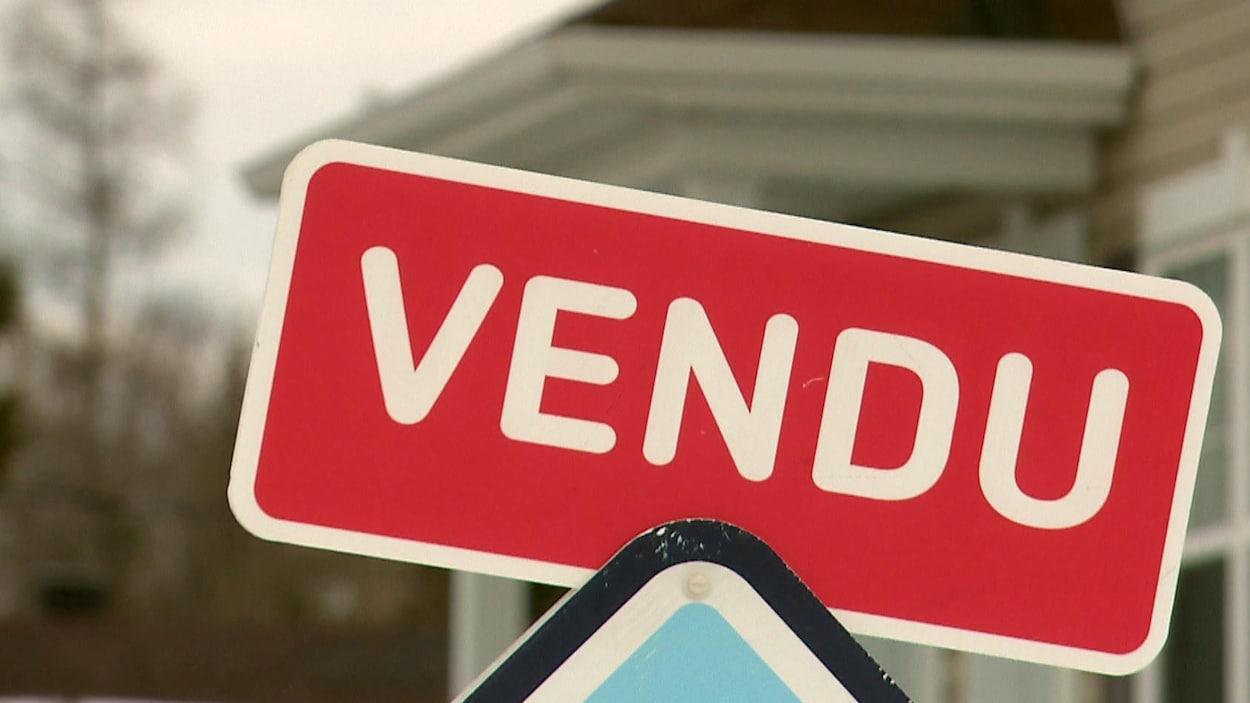 Une affiche d'agent immobilier qui indique la vente d'une maison à Québec.