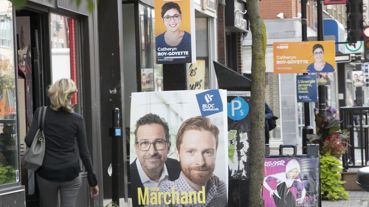 De nombreuses affiches électorales sont accrochées sur des poteaux.