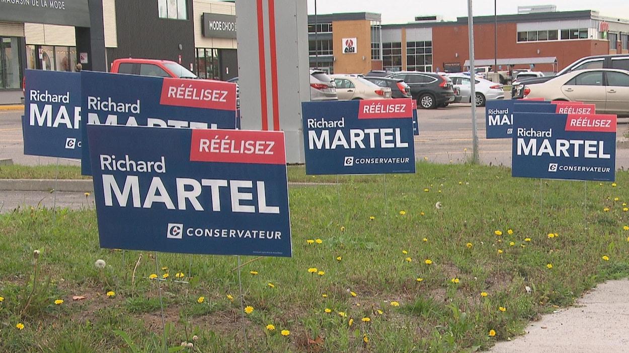 Des pancartes électorales ont été installées à proximité d'un stationnement commercial.