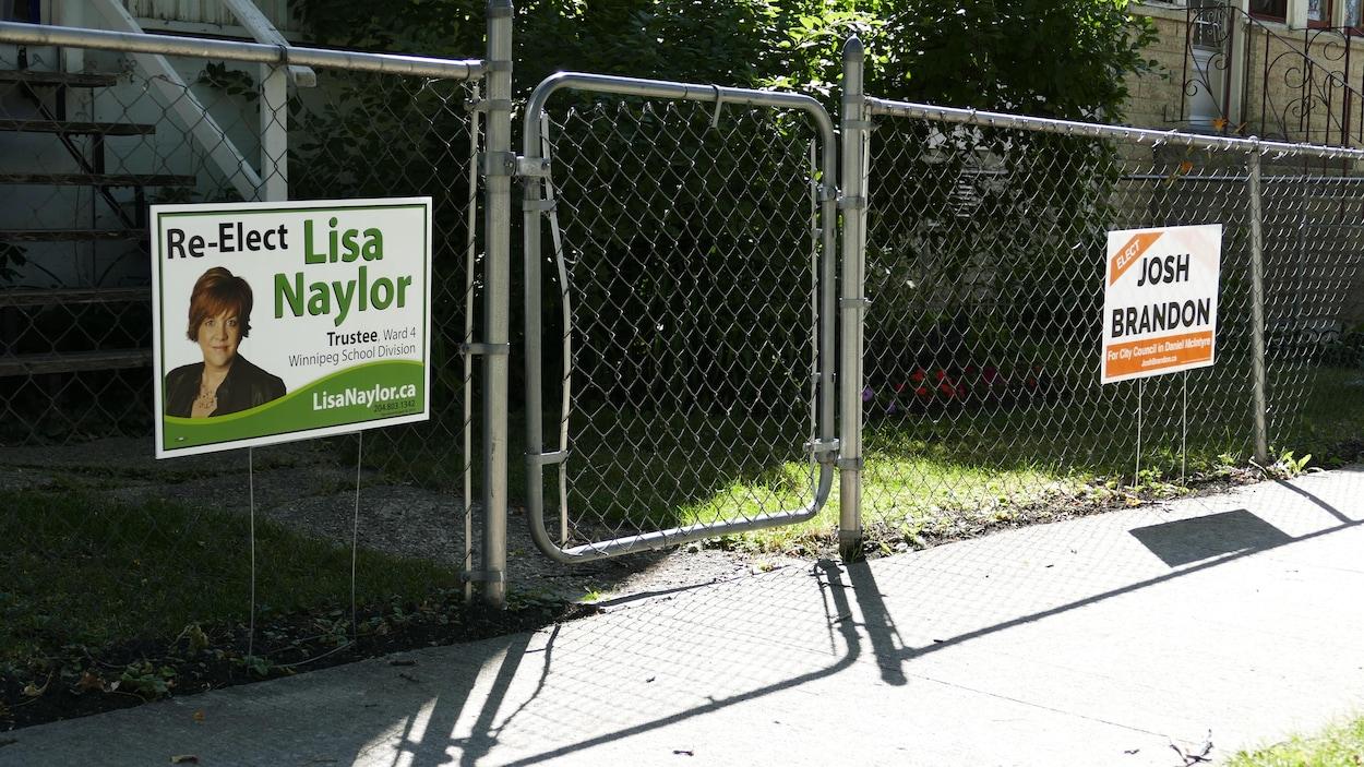 Une pancarte électorale de Lisa Naylor, candidate aux élections scolaires, et une affiche de Josh Brandon, candidat au conseil municipal, plantées devant un grillage.