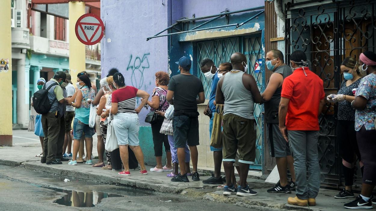 Une dizaine de personnes sont sur un trottoir de la capitale cubaine.