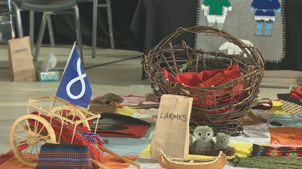 Un panier, un canot miniature en écorce, de petits jouets et un sac brun où il est écrit « Larmes ».