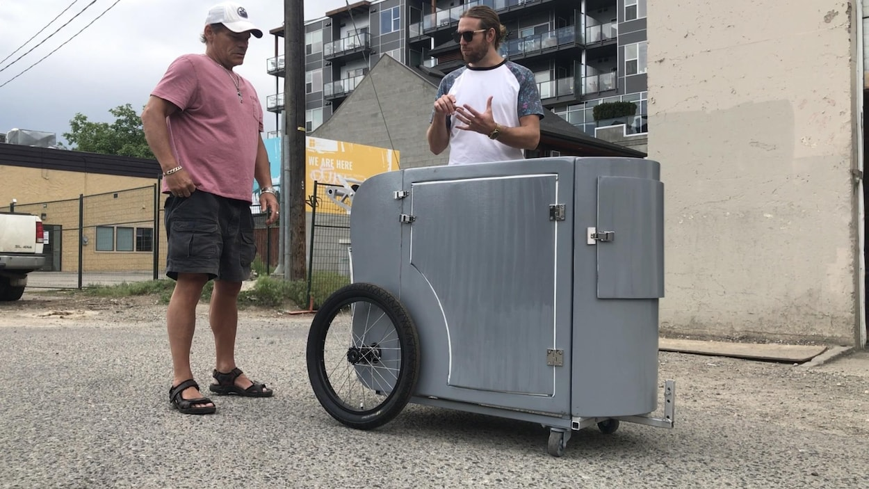 Deux hommes près du chariot gris métallique qui compte deux grandes roues à l'arrière et deux petites à l'avant.