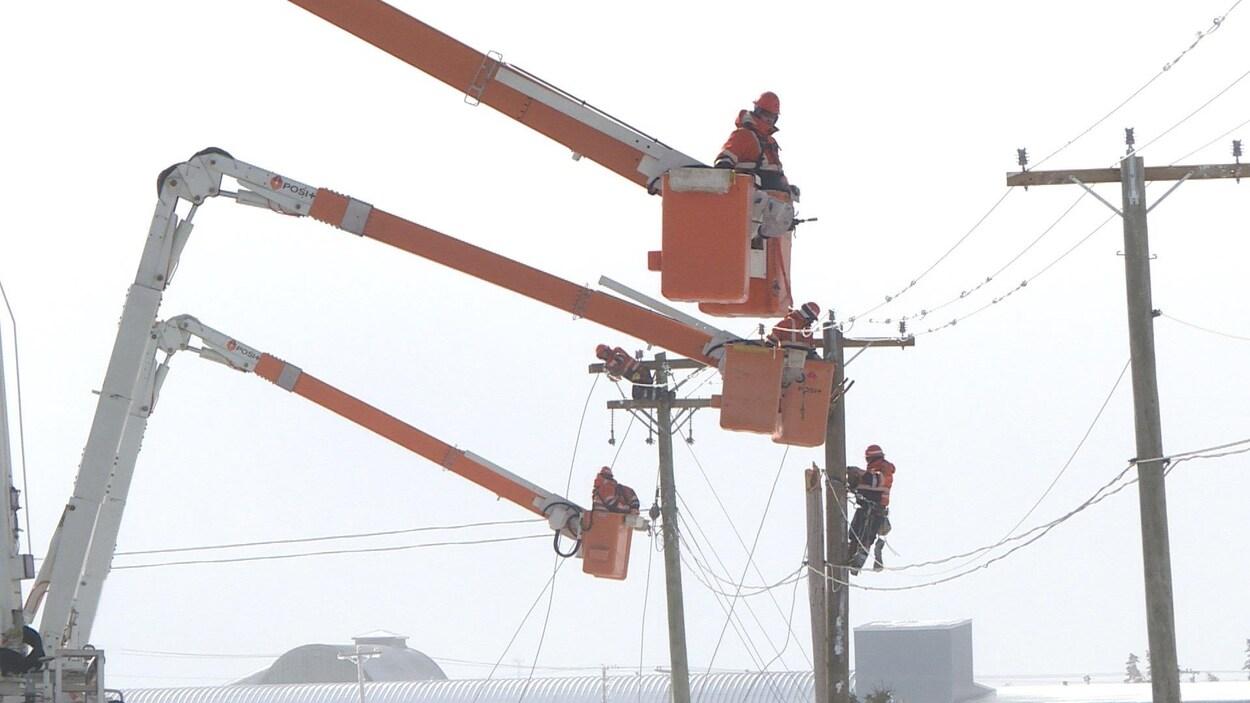Cinq monteurs de lignes sur des poteaux