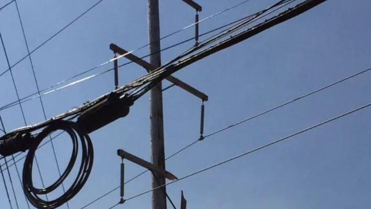 Une traverse brisée pend d'un poteau électrique.