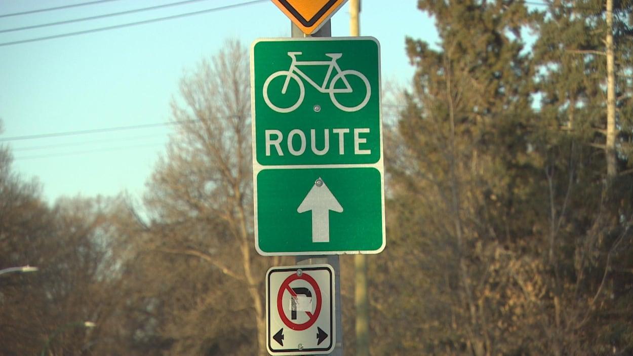 Un panneau vert avec une bicyclette dans la lumière orangée du matin.
