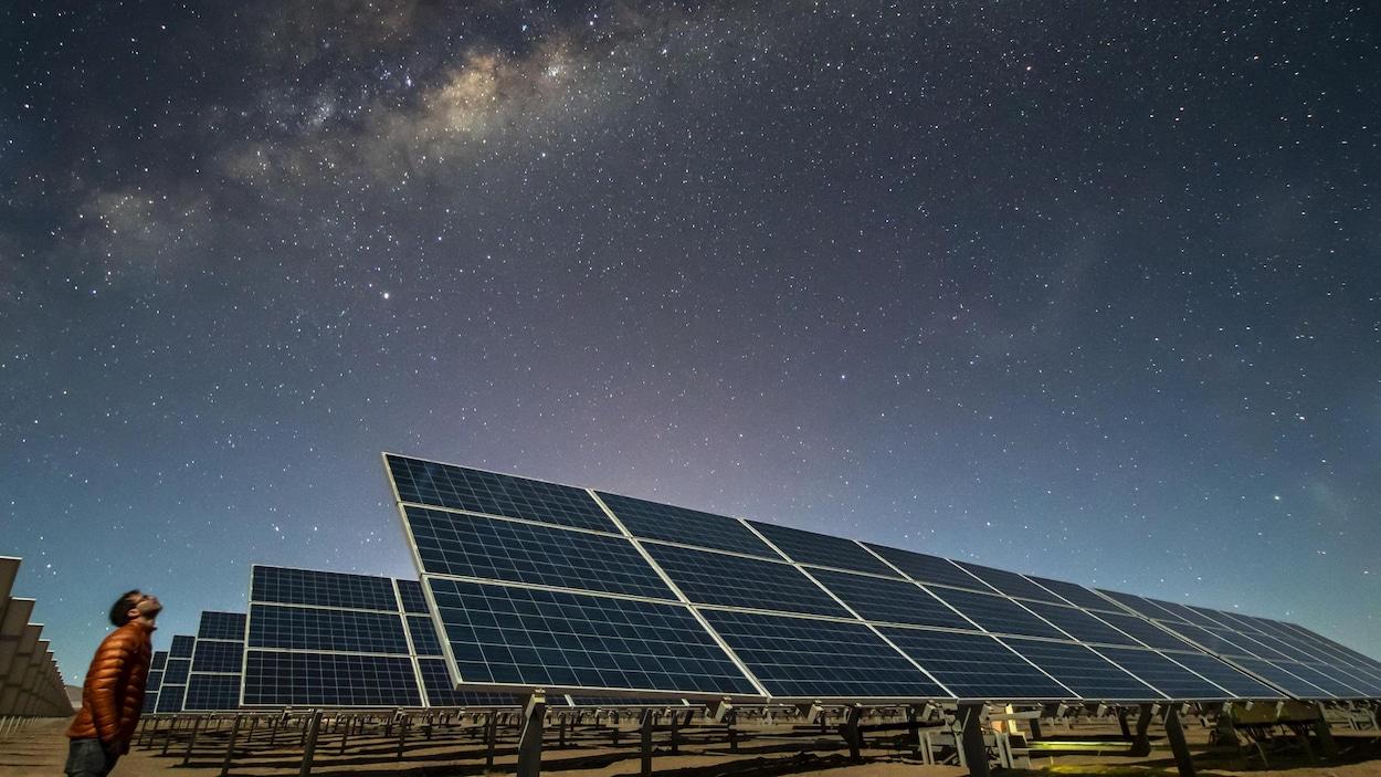 Des rangées de panneaux solaires dans un désert, la nuit.