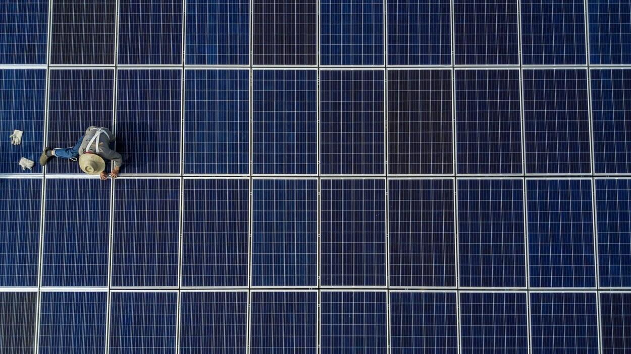 Un ouvrier chinois pose des panneaux solaires au sommet d'un immeuble de 47 étages à Wuhan.