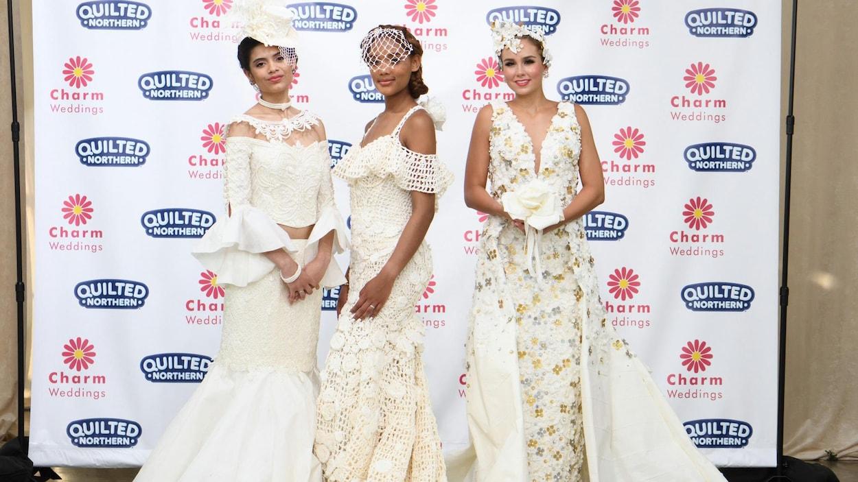Trois femmes posent dans des robes de mariage faites de papier hygiénique.