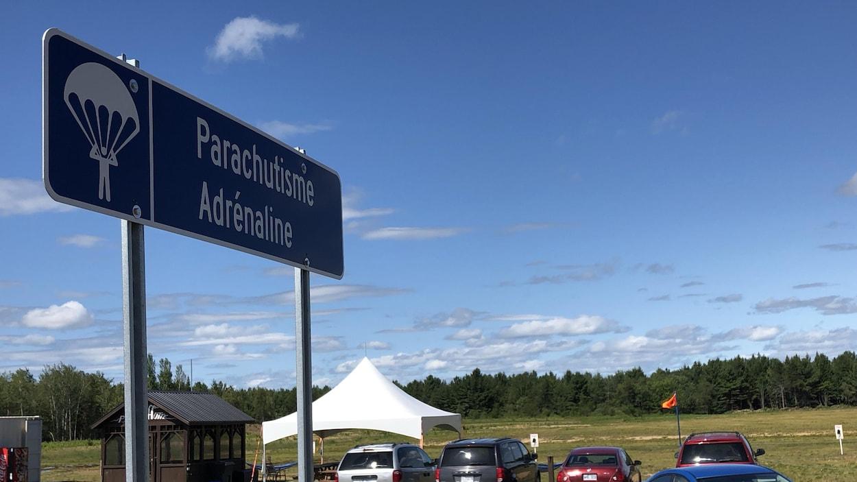 Pancarte de l'endroit avec des voitures dans le stationnement.