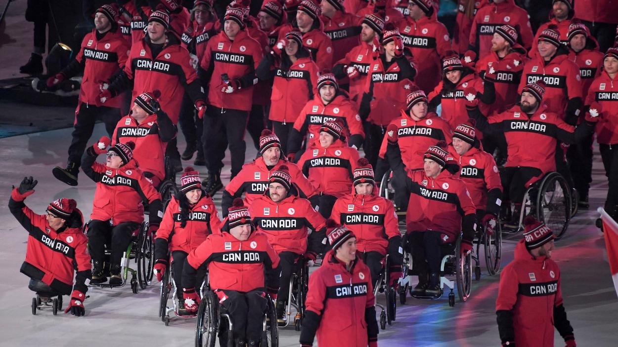 Des athlètes canadiens marchent et saluent la foule.