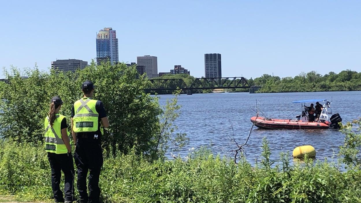 Deux ambulanciers scrutent la rivière des Outaouais sur laquelle circule un bateau des services d'urgence.