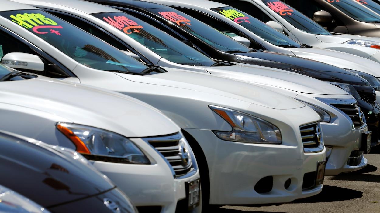 Plusieurs voitures sont stationnées dans une concession automobile avec des prix de vente affichés sur leur pare-brise