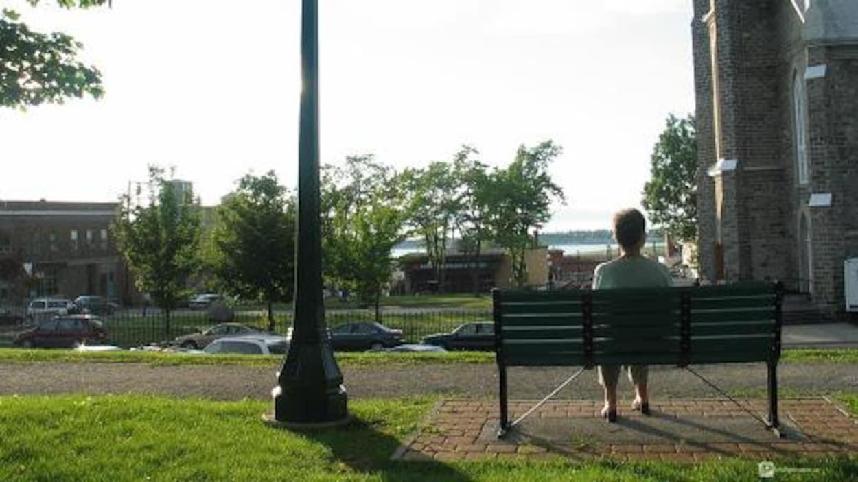 Une dame assise sur un banc de parc au Parc Blais.
