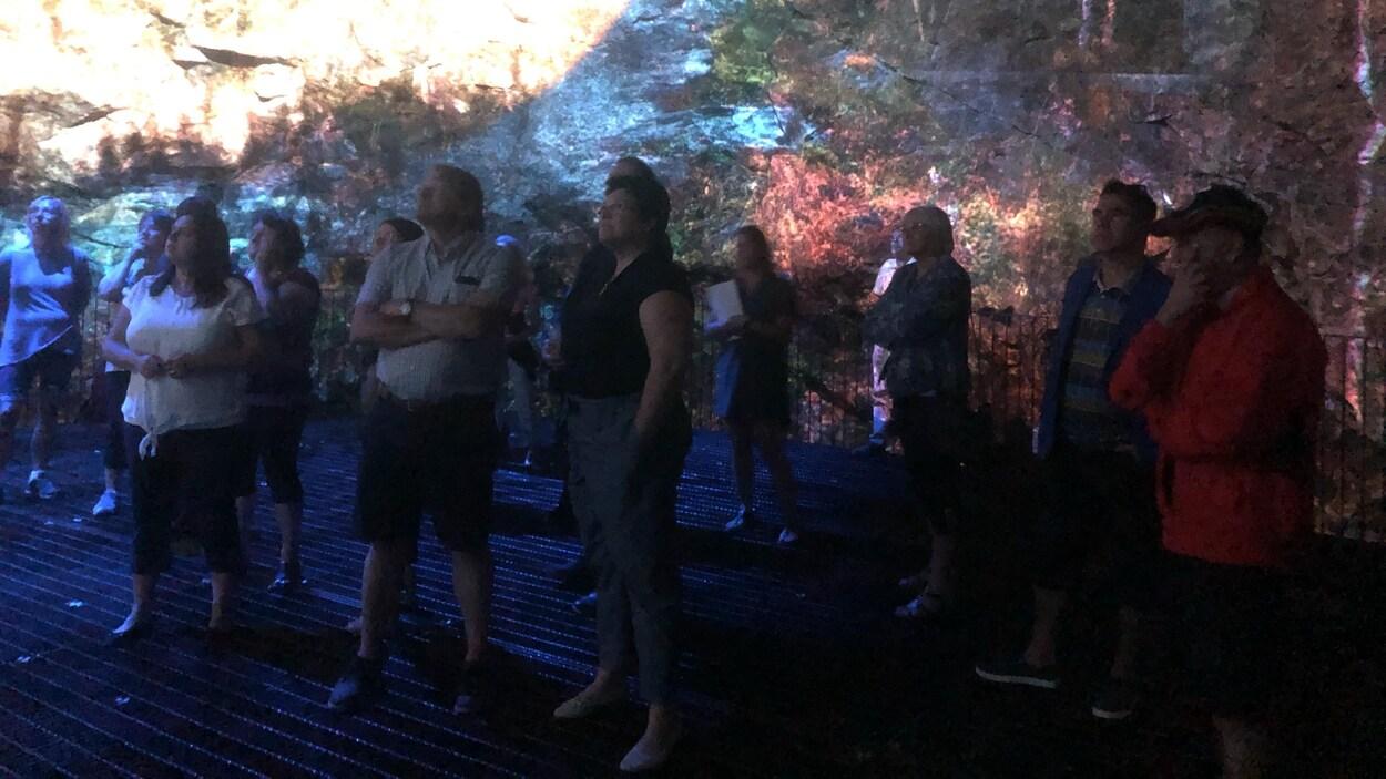 Des spectateurs assistent à un spectacle projeté sur le granit.