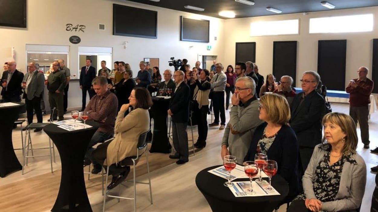 Quelques dizaines de personnes sont rassemblées dans une salle. Des verres de vin sont posés sur de petites tables noires.