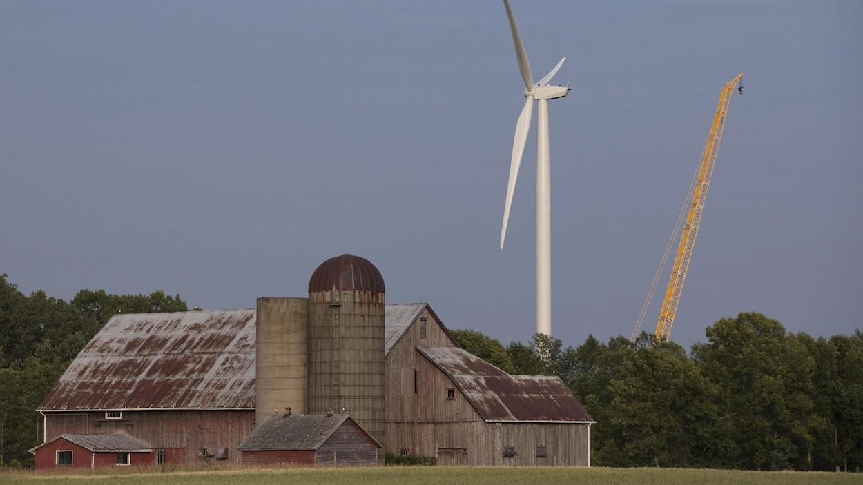 Une éolienne et une grue derrière une grange.