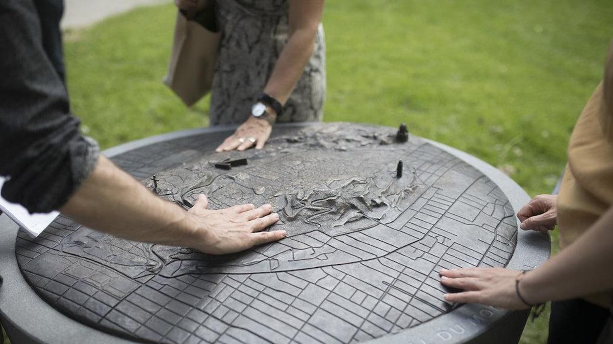 Des personnes sur de l'herbe verte touchant une pierre en forme de cylindre dont l'une des extrémités est en forme de montagnes.