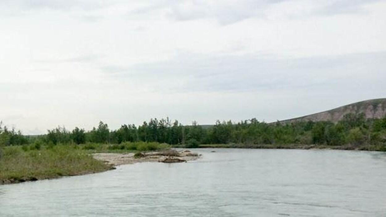 La rivière serpente à travers de petites collines.