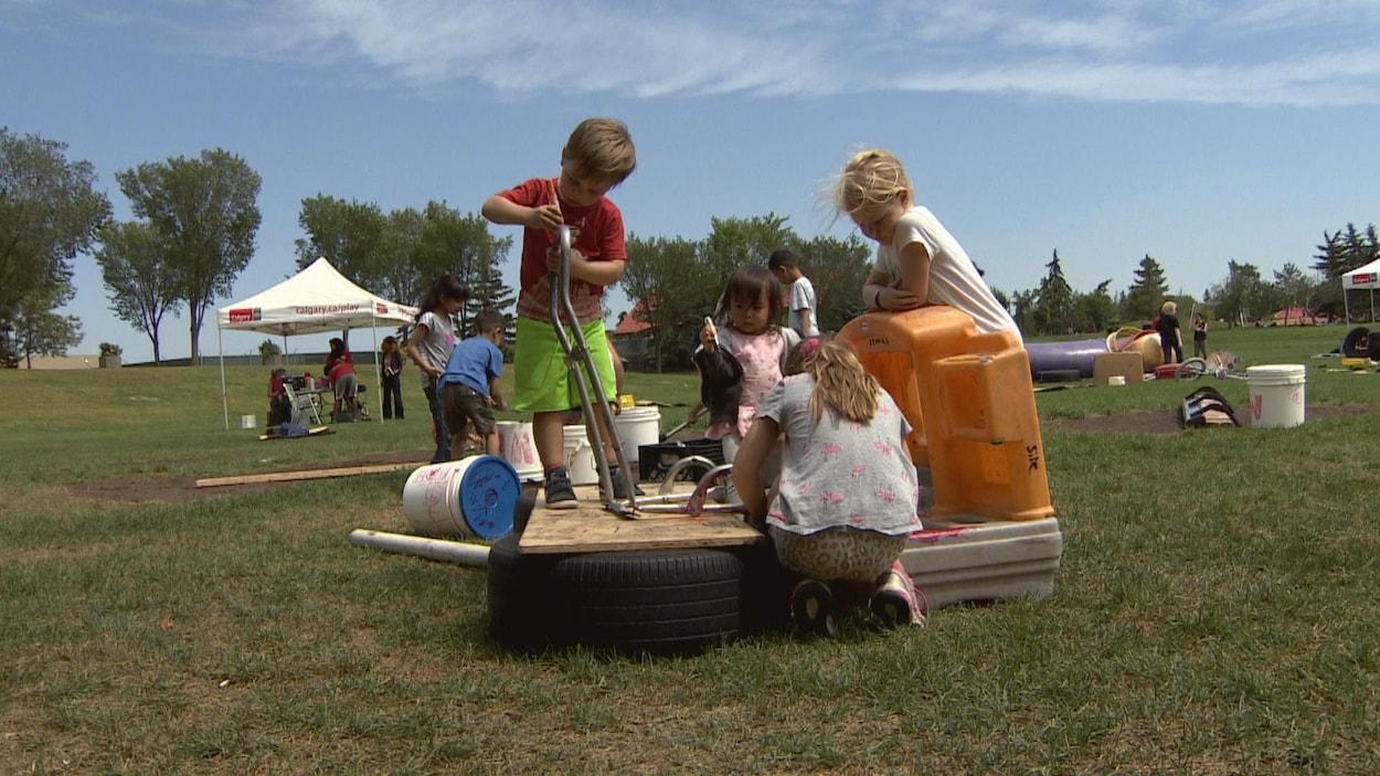 Un groupe d'enfants joue sur la plateforme qu'ils ont bâtie à l'aide de pneus, de planches de bois et de structures en plastique.