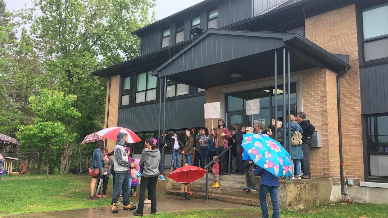 Des gens debout devant une école