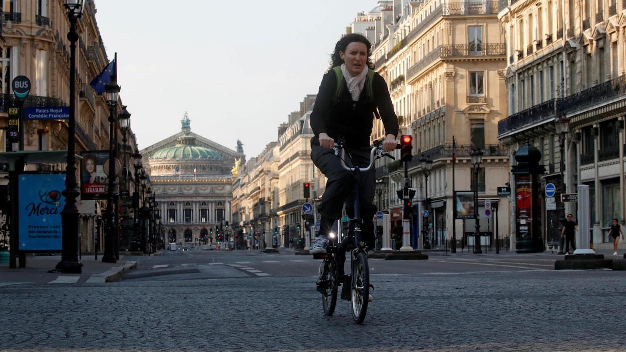 La femme est sur son vélo dans une rue vide.