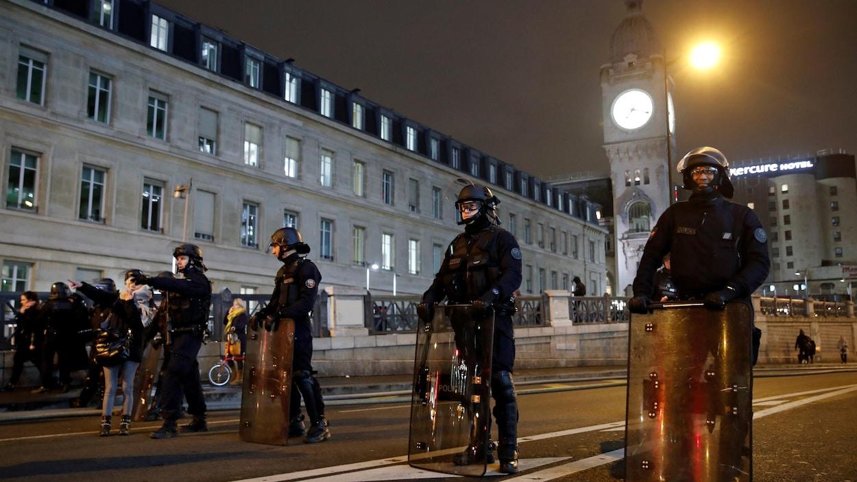 Des policiers antiémeute tiennent leurs boucliers dans la rue.