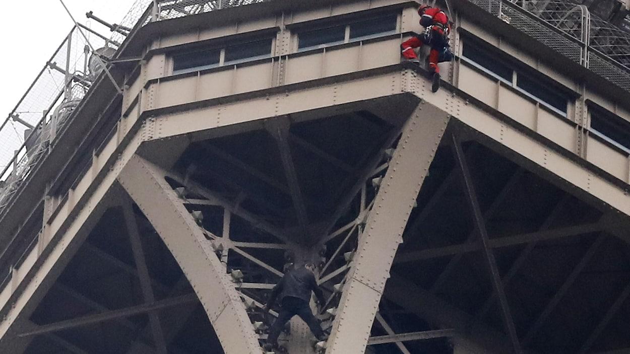 Un homme en noir se tient aux barreaux de la tour Eiffel.