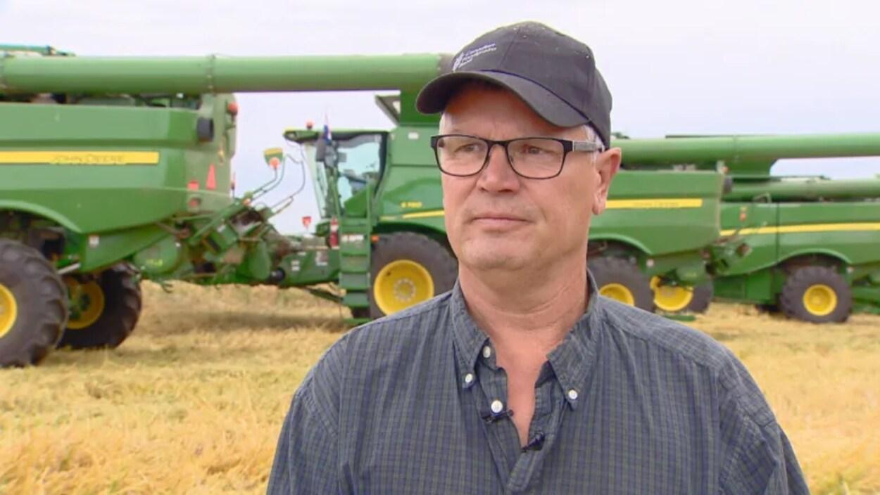 L'agriculteur Shaun Galloway dans un champ devant une moissonneuse-batteuse.