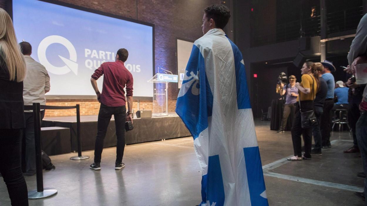 Un militant péquiste, portant le drapeau québécois comme une cape, est debout devant une estrade vide.