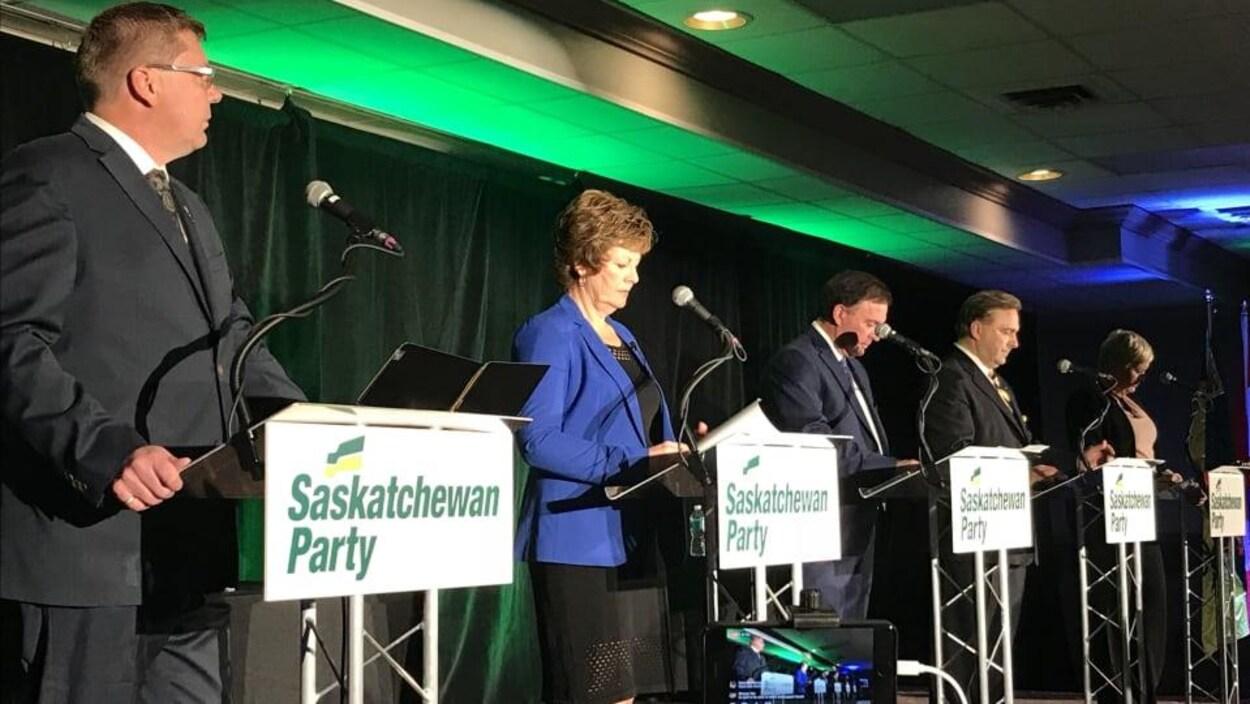 Les cinq candidats sur une scène côte à côte devant leur micro.